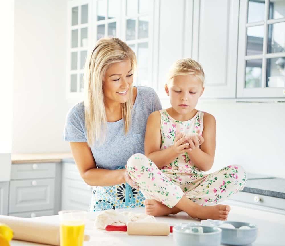 happy-woman-helping-little-girl-prepare-food-PQP7GMU_Fotor-2